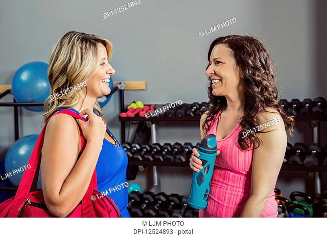 Two attractive middle-aged women talking to each other after working out at a fitness class in a gym; Spruce Grove, Alberta, Canada