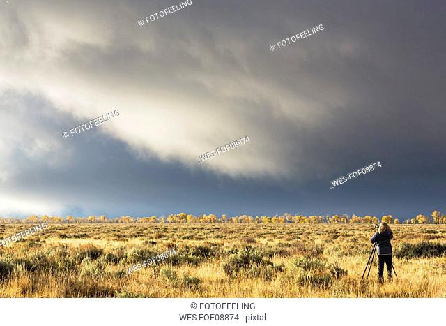 USA, Wyoming, Rocky Mountains, Grand Teton National Park, woman taking picture of the landscape