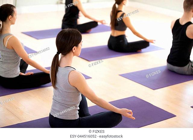 Group of young sporty people practicing yoga, doing Sukhasana exercise, Easy Seat pose, working out, indoor close up, students training in sport club, studio