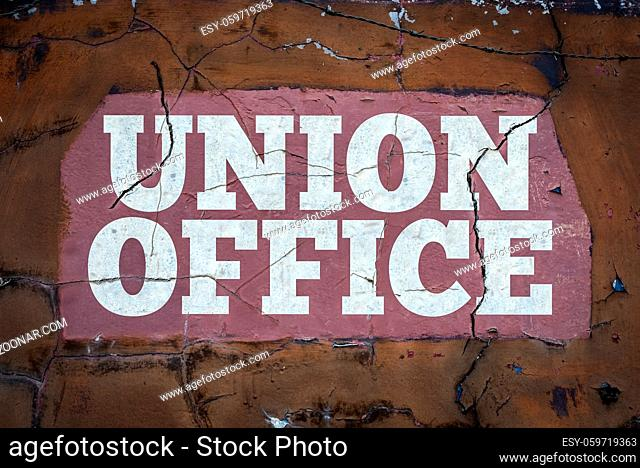 A Grungy Workers' Union Sign In Cracked White Paint At An Industrial Workplace