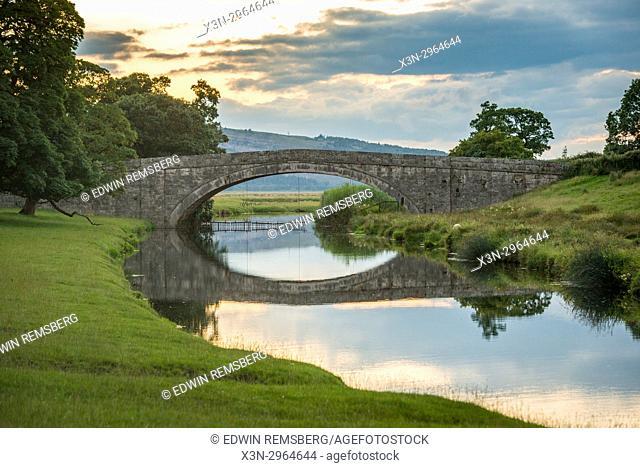 Stone bridge reflects onto water at dusk , Kirkby Longsdale, Cumbria, England