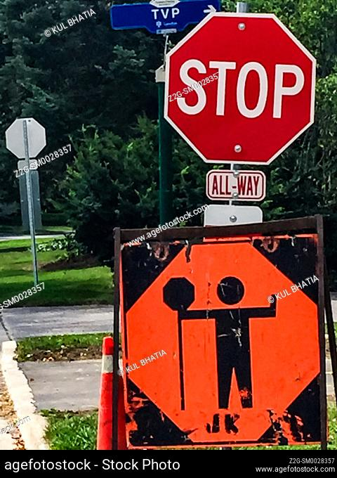 STOP sign indicating the presence of a guard directing traffic ahead at a road work site, Ontario, Canada
