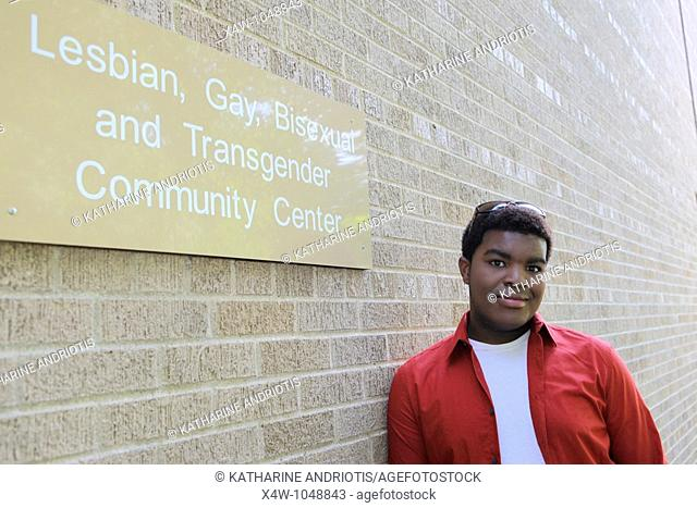 Outdoor portrait of young gay African-American man standing outside of gay community center