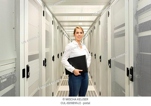 Portrait of young woman in data centre, holding laptop