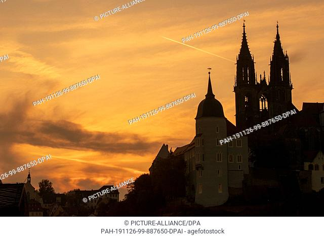 15 October 2019, Saxony, Meißen: The setting sun colors the sky behind the cathedral to Meissen orange-red. The cathedral is dedicated to St