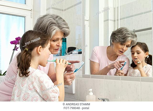 A grandmother teaching her granddaughter how to brush teeth