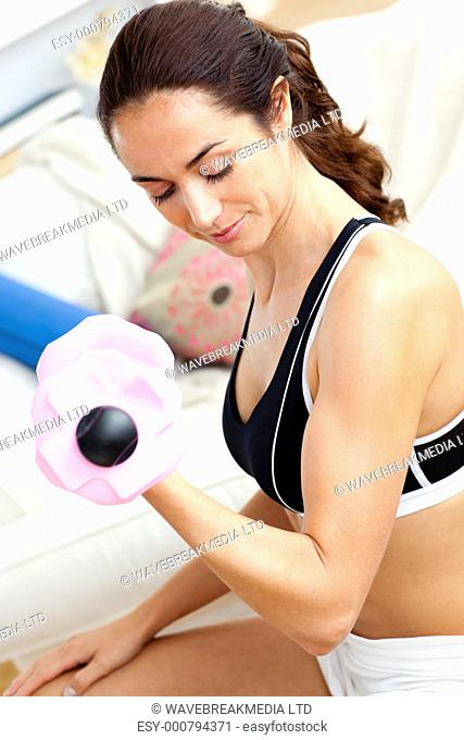 Young athletic woman holding a dumbbell in her living-room at home