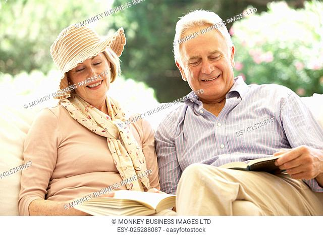 Portrait Of Senior Couple Relaxing On Sofa Reading Together