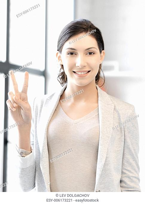 business concept - confident young woman showing v-sign