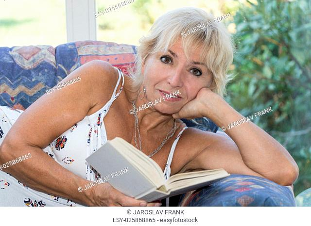 Senior mature blond woman is lying on the couch and reading a book. She looking at the camera. All potential trademarks are removed