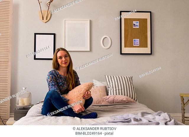 Portrait of smiling Caucasian woman sitting on bed