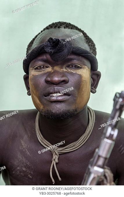 A Portrait Of A Young Man From The Mursi Tribe Holding A Gun, Mursi Village, Omo Valley, Ethiopia