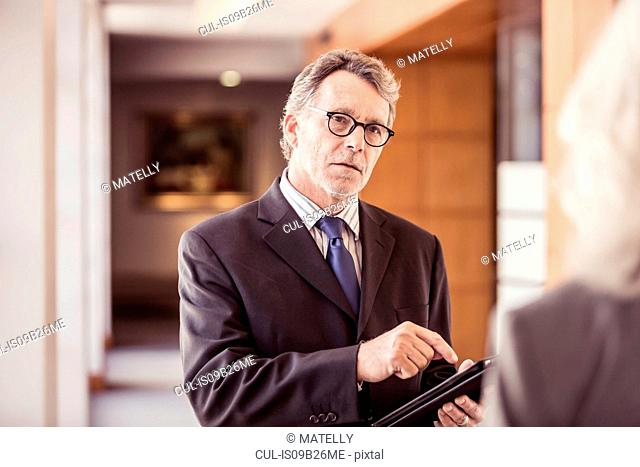 Over shoulder view of businessman using digital tablet in office corridor