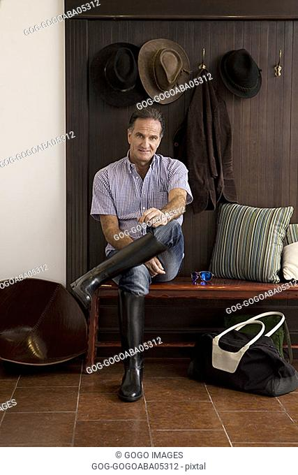 Man wearing riding boots indoors