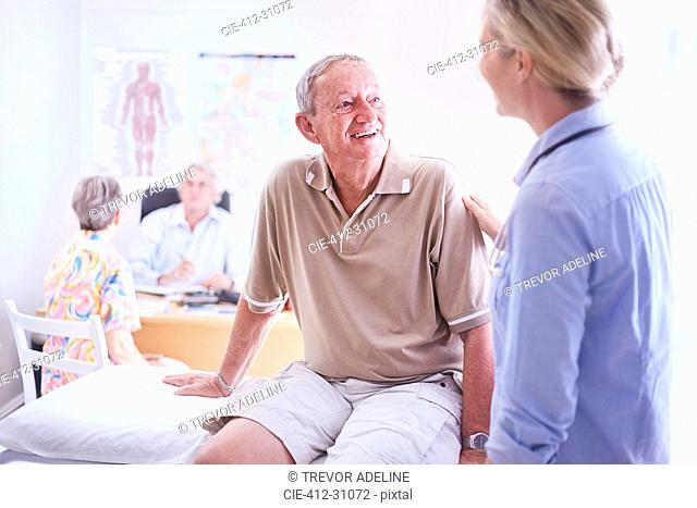Doctor talking to senior man in examination room