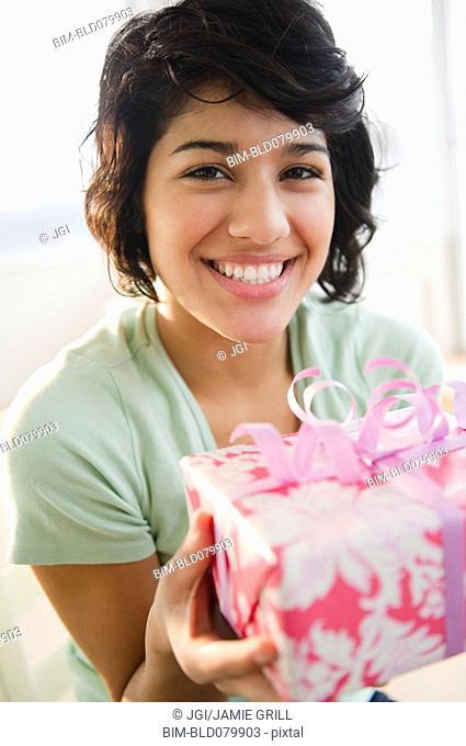 Hispanic woman holding birthday gift