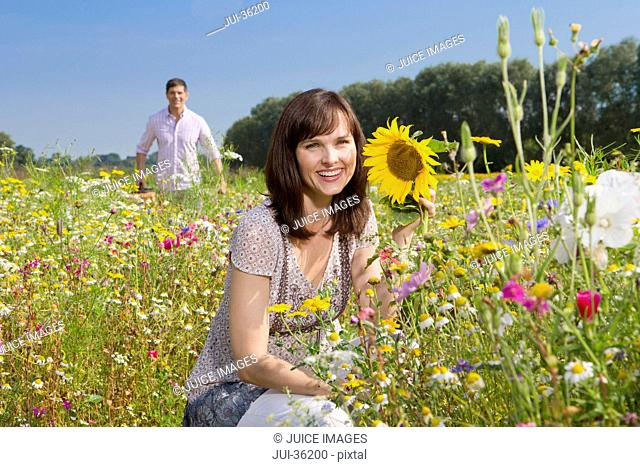 Portrait of smiling couple among wildflowers in sunny meadow