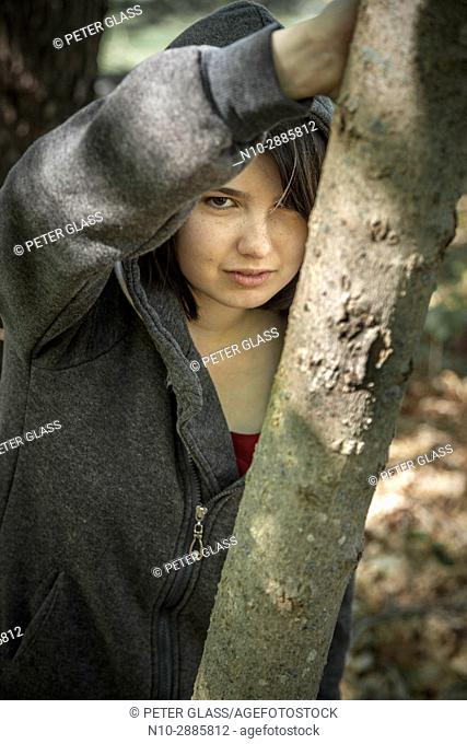 Young woman, leaning on a tree in a park, wearing a sweatshirt and hoodie