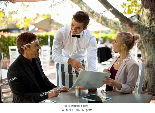 Waiter ready to serve couple seated at outdoor restaraunt