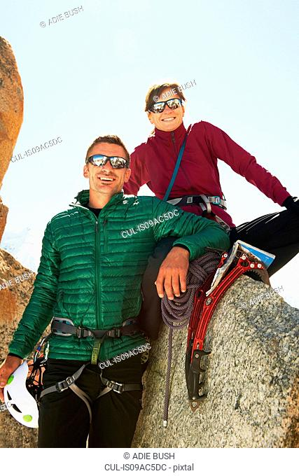 Portrait of mid adult couple with mountaineering equipment smiling