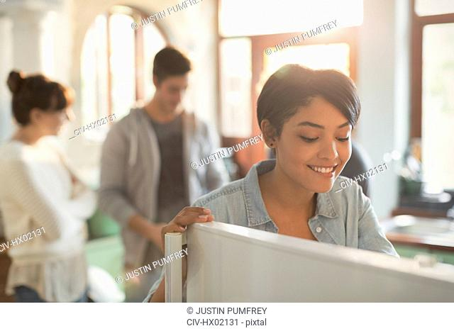 Smiling young woman looking into refrigerator in kitchen