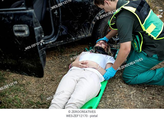 Paramedic moving car crash victim on stretcher