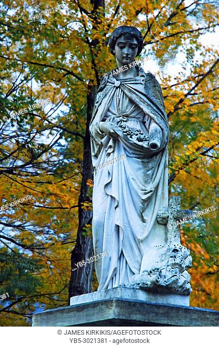 A marble statue is framed by autumn foliage in a cemetery in Vermont