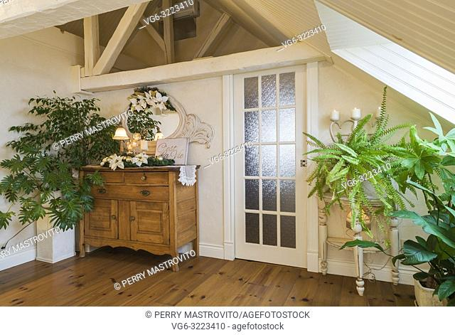 Antique maple wood dresser and green plants in master bedroom in the attic of an old circa 1840 Canadiana cottage style home