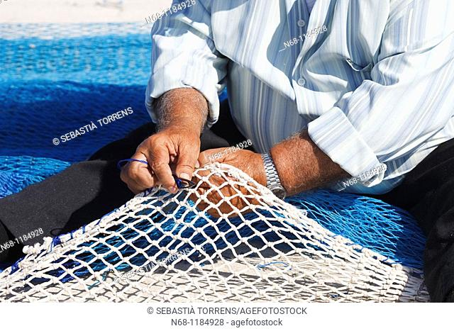 Old fisherman sewing up nets, Alcudia, M ajorca, Spain