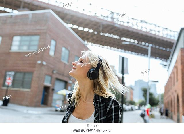 USA, New York City, Brooklyn, happy young woman listening to music with headphones in the city