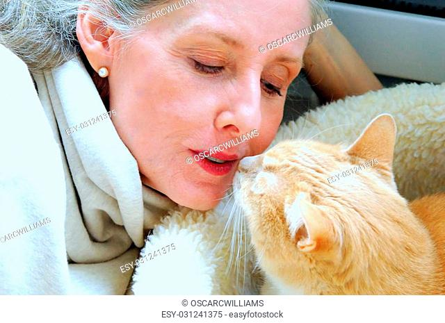 Mature female blond beauty bonding with her cat indoors