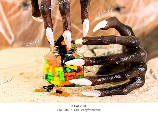 Halloween witch hands reaching for the colorful sweets