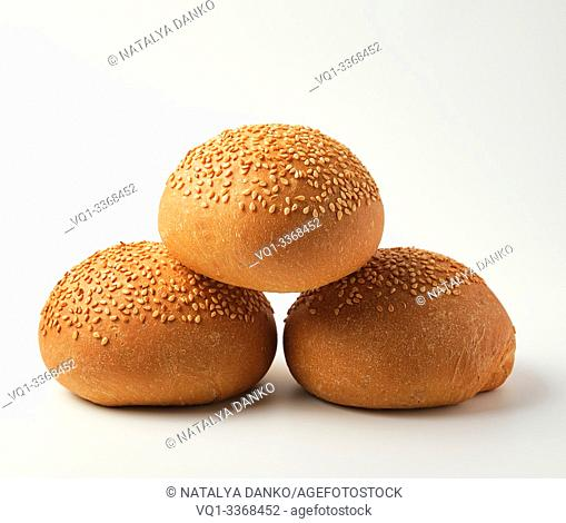 stack of baked whole round bun with sesame seeds made from white wheat flour on a white background