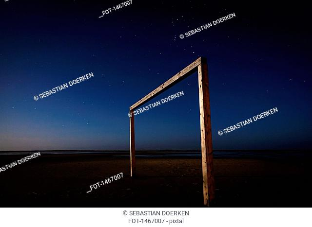 Soccer goal on beach at night