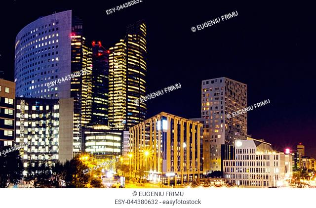 Paris city at night with business centers and glass towers with lights, France