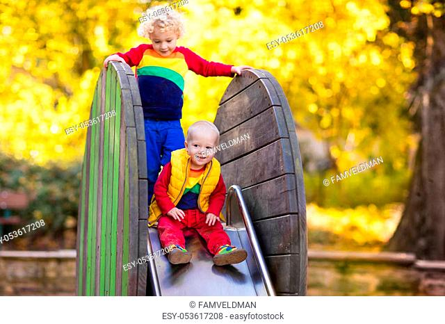 Kids on playground Children play in autumn park. Child on slide and swing on sunny fall day. Preschool or kindergarten yard. Daycare for young kid