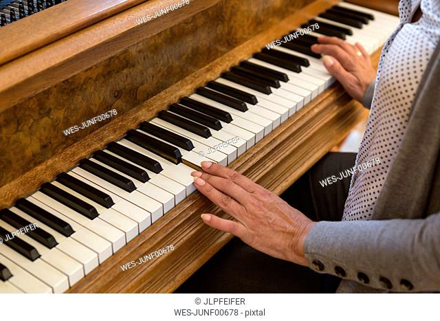 Hands of woman playing piano, close-up