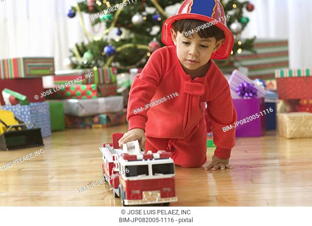 Little boy playing with a fire truck in front of Christmas tree