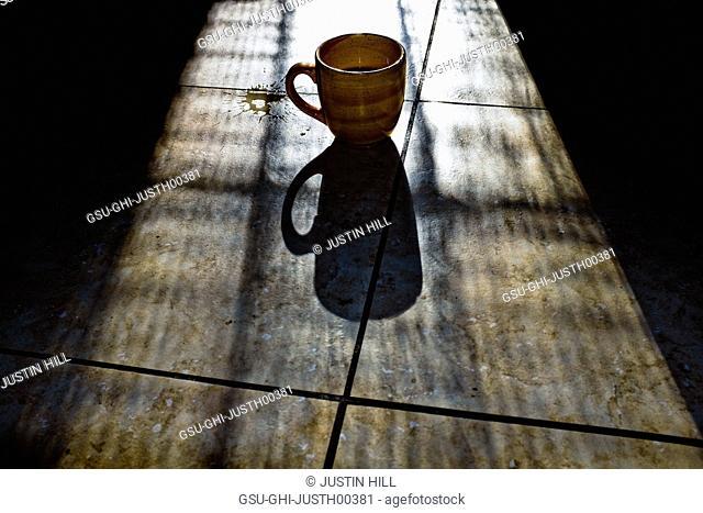 Coffee Mug With Shadow on Tile Floor