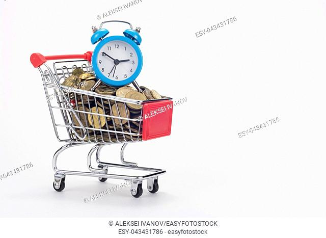 The grocery cart of the store is filled with coins, with a small table clock on top