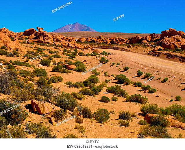 Landscape of Altiplano with rocks, white lagoon and peaks. Sunny clear blue sky day. Bolivia