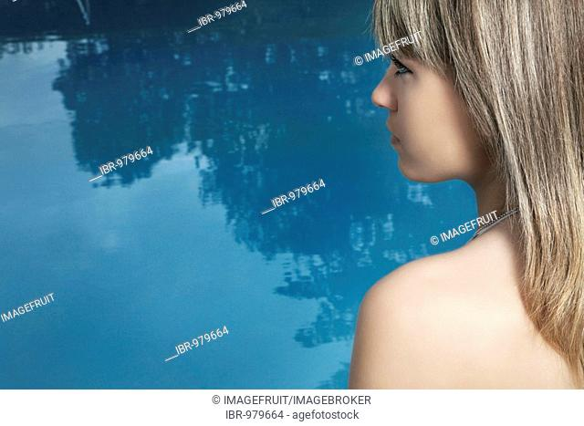 Young dark-blond woman at a swimming pool