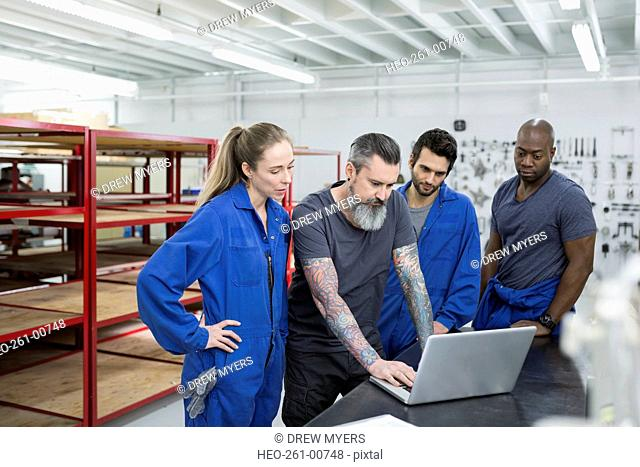 Helicopter mechanics working at laptop in workshop