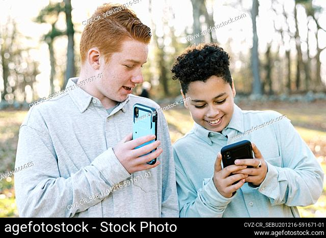 Two tween mixed race brothers playing game on smart phone