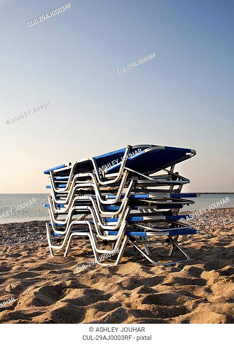 Stack of sunloungers on the beach