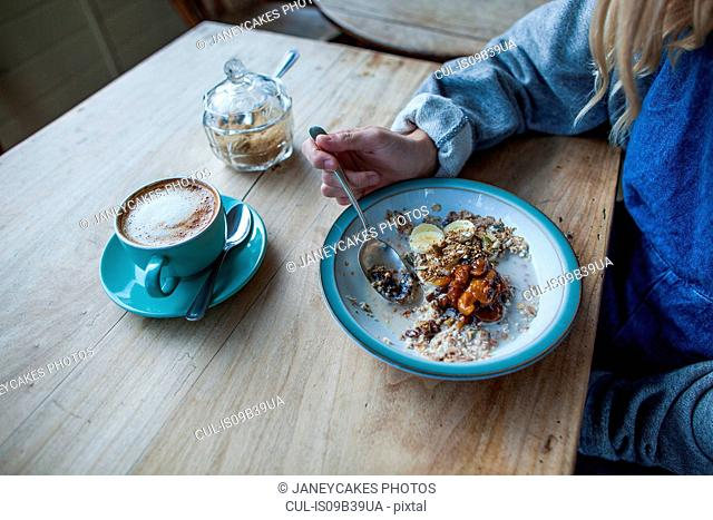 Young woman in cafe, eating muesli, mid section