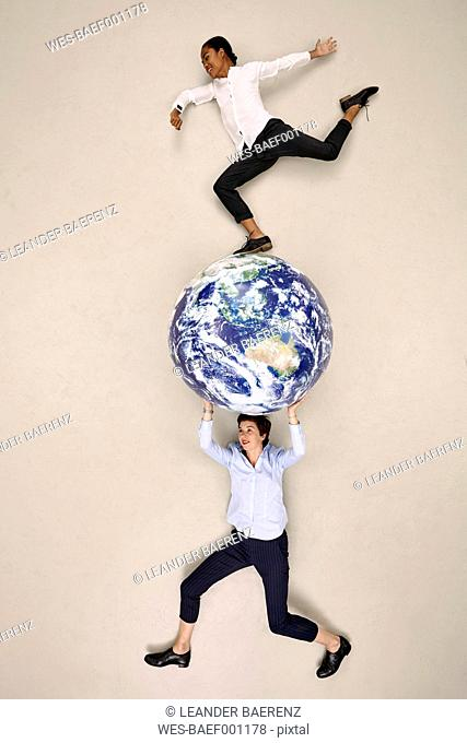 Businesswoman carrying globe with colleague on top