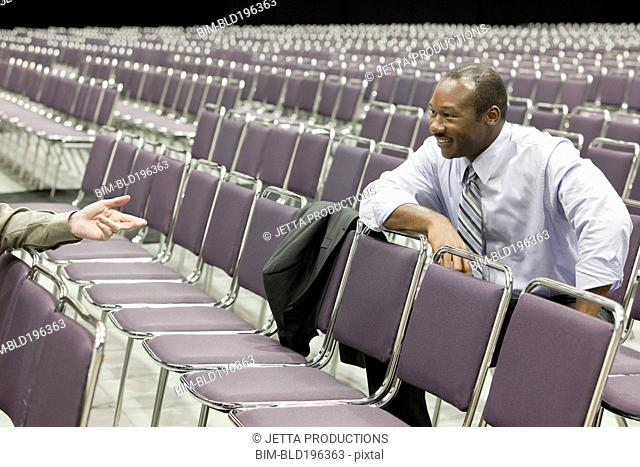 Businesspeople talking in empty conference center