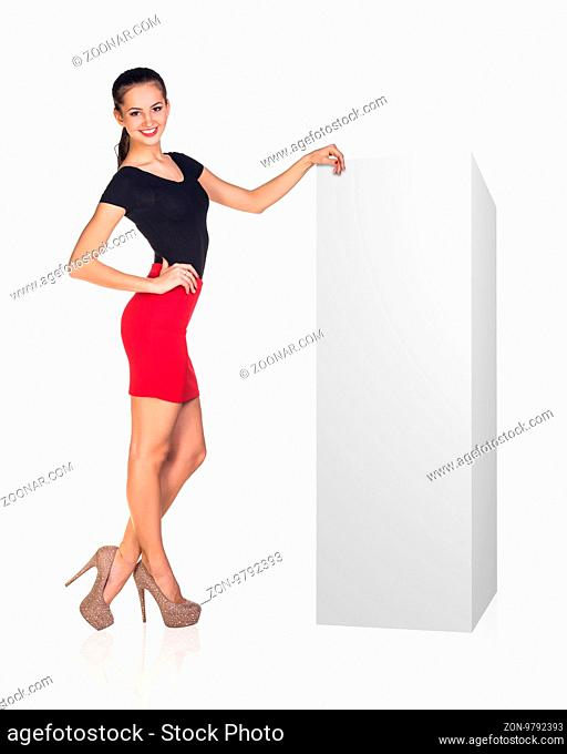 Young business woman leaned on white blank box. Presents product. Isolated on white
