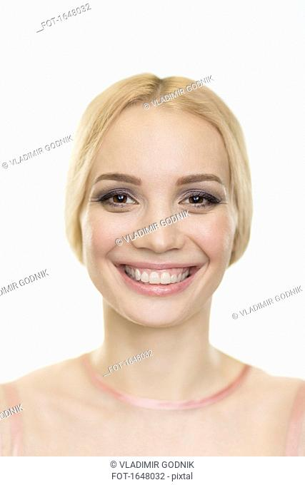 Close-up portrait of smiling fashion model against white background